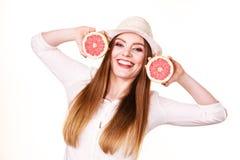 La mujer sostiene dos halfs de agrios del pomelo en manos Fotografía de archivo libre de regalías