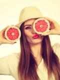 La mujer sostiene dos halfs de agrios del pomelo en manos Foto de archivo libre de regalías