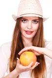 La mujer sostiene dos halfs de agrios del pomelo en manos Imagen de archivo
