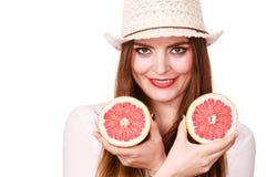 La mujer sostiene dos halfs de agrios del pomelo en manos Foto de archivo