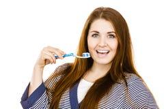 La mujer sostiene el cepillo de dientes con goma Imagen de archivo libre de regalías