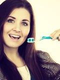 La mujer sostiene el cepillo de dientes con goma Fotos de archivo