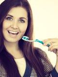 La mujer sostiene el cepillo de dientes con goma Imágenes de archivo libres de regalías