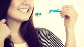 La mujer sostiene el cepillo de dientes con goma Imagen de archivo