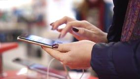 La mujer sostiene el smartphone disponible Opinión del primer de las manos femeninas que sostienen smartphone, usando la pantalla almacen de video