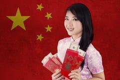 La mujer sostiene el sobre rojo con la bandera de China Imágenes de archivo libres de regalías