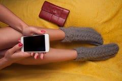 La mujer sostiene el teléfono elegante Fotos de archivo libres de regalías