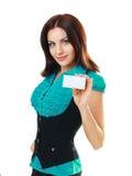 La mujer sostiene hacia fuera una tarjeta del asunto o de crédito Imágenes de archivo libres de regalías