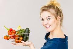 La mujer sostiene la cesta de compras con las verduras Imágenes de archivo libres de regalías