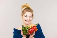 La mujer sostiene la cesta de compras con las verduras Fotos de archivo
