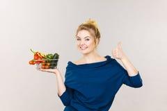 La mujer sostiene la cesta de compras con las verduras Imagen de archivo libre de regalías