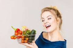 La mujer sostiene la cesta de compras con las verduras Foto de archivo