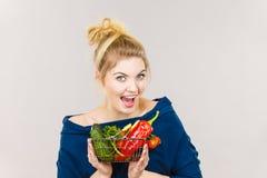La mujer sostiene la cesta de compras con las verduras Imagen de archivo
