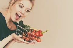 La mujer sostiene la cesta de compras con las verduras Fotografía de archivo libre de regalías
