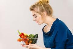 La mujer sostiene la cesta de compras con las verduras Foto de archivo libre de regalías