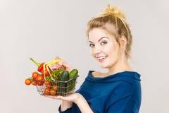 La mujer sostiene la cesta de compras con las verduras Fotografía de archivo