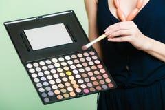 La mujer sostiene la paleta y el cepillo profesionales del maquillaje Foto de archivo