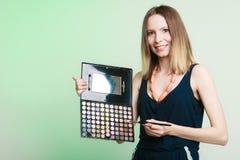 La mujer sostiene la paleta y el cepillo profesionales del maquillaje Imagen de archivo libre de regalías