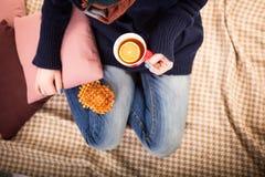 La mujer sostiene la taza caliente de té o de café, calentándose las manos Foto de archivo