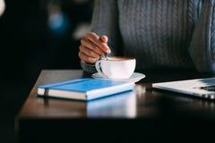 La mujer sostiene la taza de café caliente, calentándose las manos Imagen de archivo