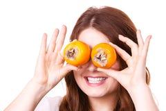 La mujer sostiene las frutas del caqui del caqui en los ojos, aislados imágenes de archivo libres de regalías