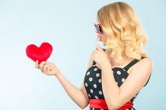 La mujer sostiene símbolo rojo del amor del corazón y el caramelo de la piruleta Imagen de archivo libre de regalías