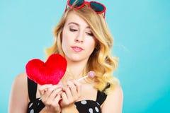 La mujer sostiene símbolo rojo del amor del corazón y el caramelo de la piruleta Fotografía de archivo