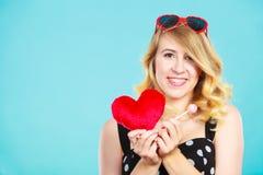 La mujer sostiene símbolo rojo del amor del corazón y el caramelo de la piruleta Foto de archivo