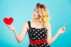La mujer sostiene símbolo rojo del amor del corazón y el caramelo de la piruleta Fotografía de archivo libre de regalías