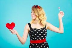 La mujer sostiene símbolo rojo del amor del corazón y el caramelo de la piruleta Foto de archivo libre de regalías