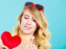 La mujer sostiene símbolo rojo del amor del corazón y el caramelo de la piruleta Imagen de archivo