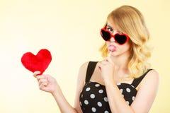 La mujer sostiene símbolo rojo del amor del corazón y el caramelo de la piruleta Imágenes de archivo libres de regalías