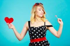 La mujer sostiene símbolo rojo del amor del corazón y el caramelo de la piruleta Imagenes de archivo