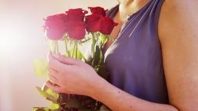 La mujer sostiene un ramo de rosas rojas Imagen de archivo