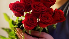 La mujer sostiene un ramo de rosas rojas Fotos de archivo