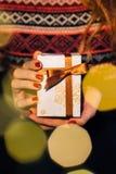 La mujer sostiene un regalo de la Navidad Foto de archivo