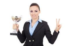 La mujer sostiene un trofeo y hace la muestra de la victoria imagenes de archivo