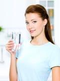 La mujer sostiene un vidrio con agua Fotografía de archivo libre de regalías