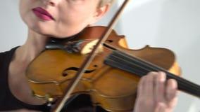 La mujer sostiene un violín que juega su inclinación sobre las secuencias Cierre para arriba Fondo blanco almacen de metraje de vídeo