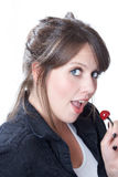 La mujer sostiene una cereza cerca de su boca Foto de archivo