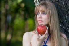 La mujer sostiene una manzana roja Imagenes de archivo
