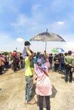 La mujer sostuvo el paraguas para su marido e hijo mientras que miraba la demostración aeroacrobacia en el salón aeronáutico 2017 fotografía de archivo libre de regalías