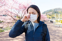 La mujer sufre de alergia de la alergia del polen en la estación de Sakura Fotos de archivo libres de regalías