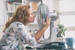 La mujer sufre de calor en la oficina o en casa Foto de archivo