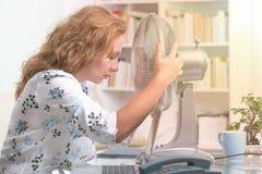 La mujer sufre de calor en la oficina o en casa imagen de archivo