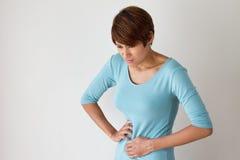 La mujer sufre de dolor de la menstruación o de dolor de estómago Imagenes de archivo