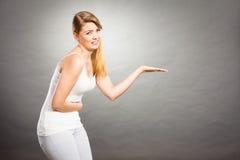 La mujer sufre de la mano abierta de los controles del dolor del vientre Imagenes de archivo