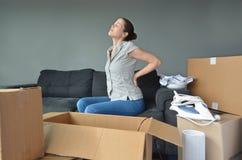 La mujer sufre del dolor de espalda debido a desempaquetar las cajas Foto de archivo