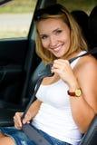La mujer sujeta un cinturón de seguridad en coche Imágenes de archivo libres de regalías