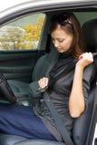 La mujer sujeta un cinturón de seguridad en el coche Imagen de archivo libre de regalías